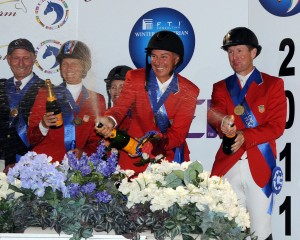 Mario Deslauriers and McLain Ward spray champagne from the winners' podium of the Nations' Cup with teammates Beezie Madden and Margie Engle, as Coach George Morris celebrates with them.