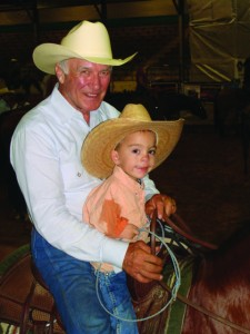 Larry mahan takes a young cowboy for a ride.